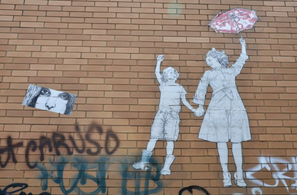 On a brown brick building, a wheatpaste of a mother holding a child's hand and she is holding a red and white parasol in the other.
