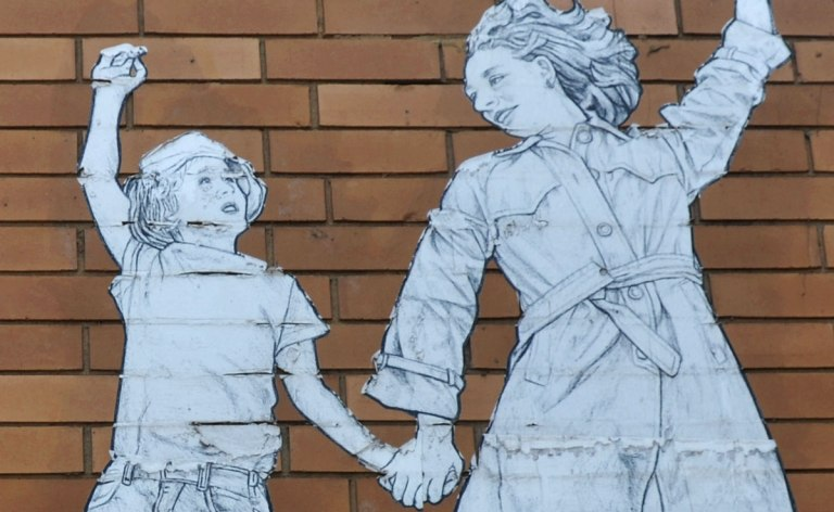 On a brown brick building, a wheatpaste of a mother holding a child's hand and she is holding a red and white parasol in the other. Close up of the upper part of the people