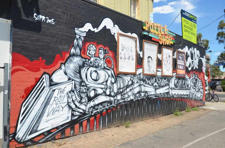 Mural of a train on a wall, along the side of the Railway Hotel