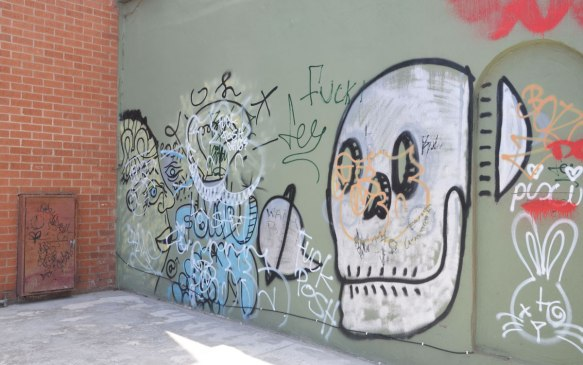 Graffiti on a cement wall. A man's face, a skull and a rabbit, all scrawled.