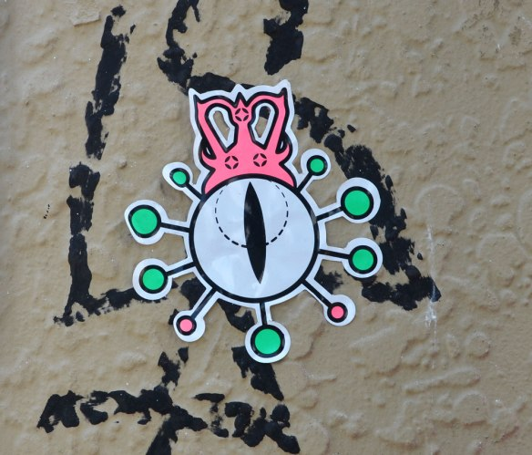 A sticker on a grey wall. White circle with green dots around it, a little pink blob creature sitting on top of it