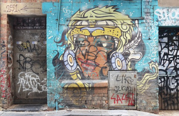 street apinting of a head, person with curly white and yellow hair that looks like the head of an animal, brown face, on a blue background, on a wall between two doors.