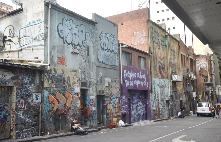 buildings in an alley with graffiti all over them. A man is sitting on the kerb in front of one of the buildings