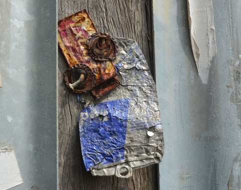 nailed to a wooden telephone pole is a little creature made from a flattened pop can, another metal label and two bottle caps for eyes.