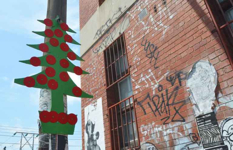 A green cutout in the shape of a Christmas tree attached high up on a telephone pole. red circles are attached to it to look like tree ornaments.