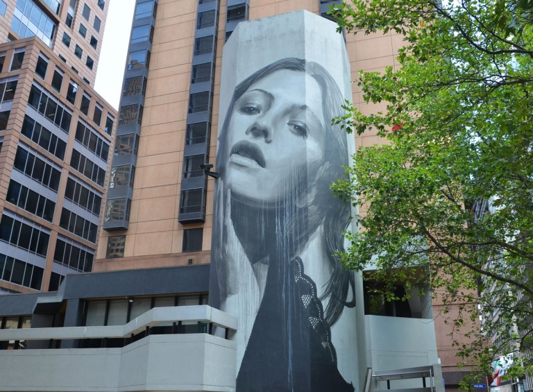 Large mural of a woman's head on a building, black and white and gray, one hand is touching her cheek.