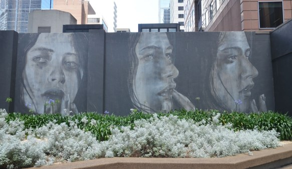 mural in grey tones of three women's heads on black background. Flower garden in front of them, city buildings behind them.