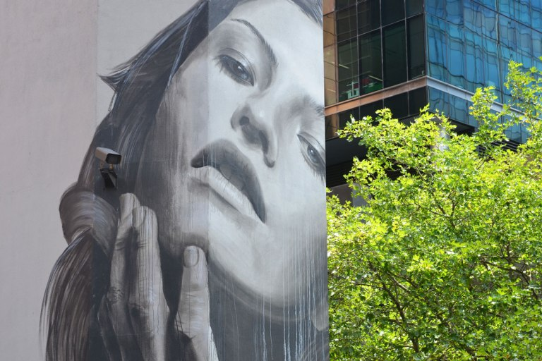 close up of Large mural of a woman's head on a building, black and white and gray, one hand is touching her cheek.