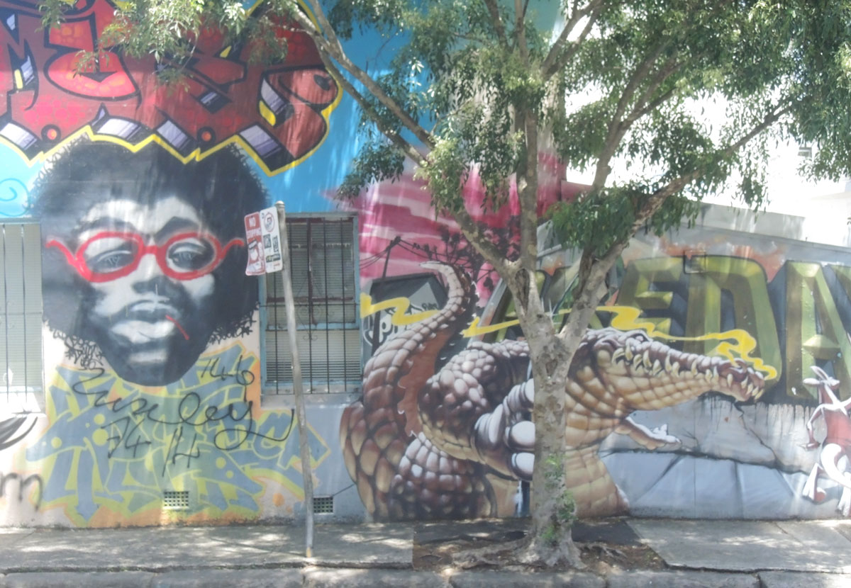 A mural on a wall, includes a black man with beard and mustache and red rimmed glasses, also includes a realistic looking crocodile