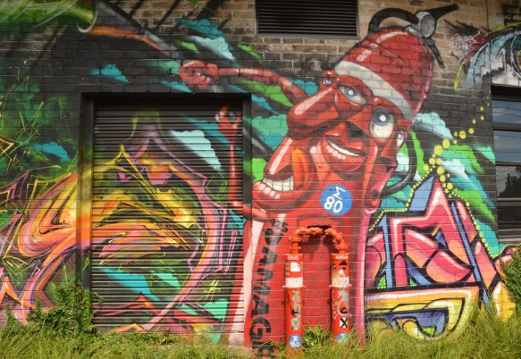 street art of what looks like a tall red fire hydrant with at least two faces, on on the front and one on the side. Arms are hoses, smiling,