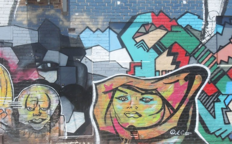 part of a larger mural in an alley, two faces in bright colours,
