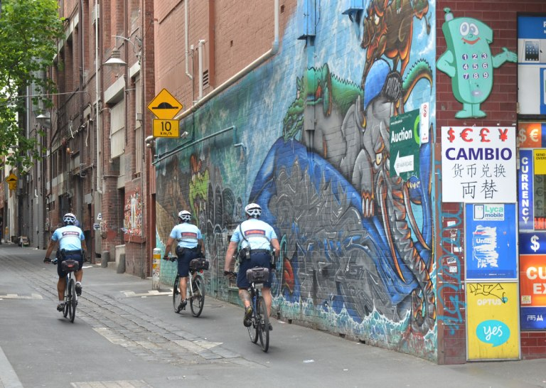 Three policemen on bikes ride down a lane past a street art mural