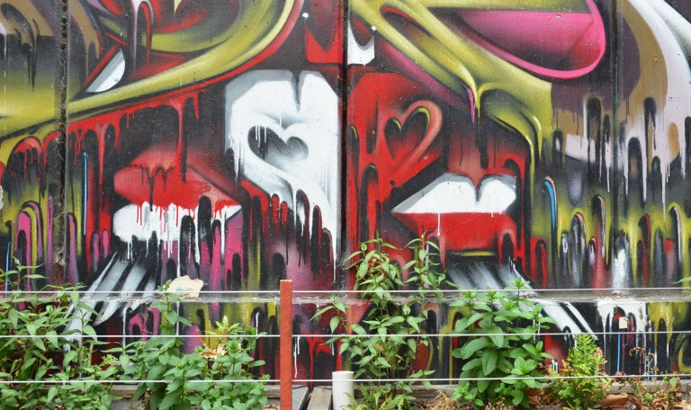 the bottom part of a mural behind a row of plants. heart shapes in red and white with paint dripping downwards