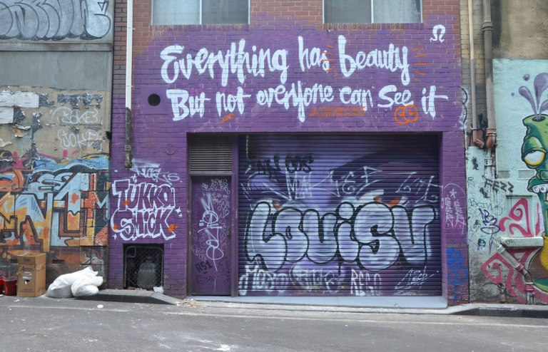 Purple building with the words Everything has beauty but not everyone can see it. The wall has a large tag LouisV written on it. Tukka Smick is written over the door.