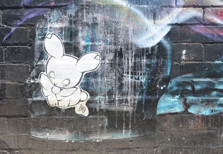 a wheatpaste bunny, white with black outline on a wall with a faded outline of a head in profile, otherwise painted black and blue