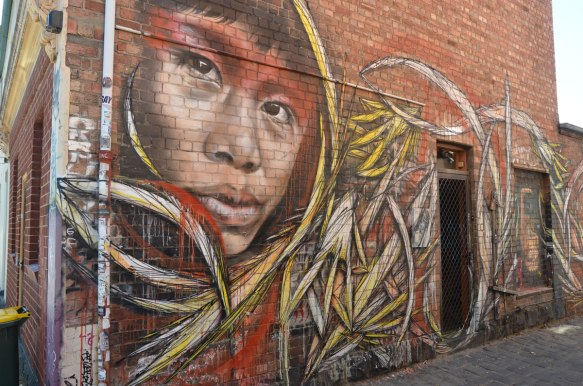in an alley, mural of a person's face, looking over his/her shoulder at the street