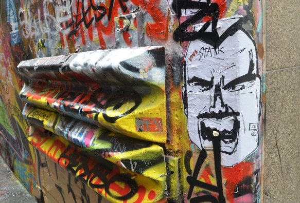 a man's face wheatpaste in the foreground and a double metal guard rail mounted on a wall and covered with graffiti in the background