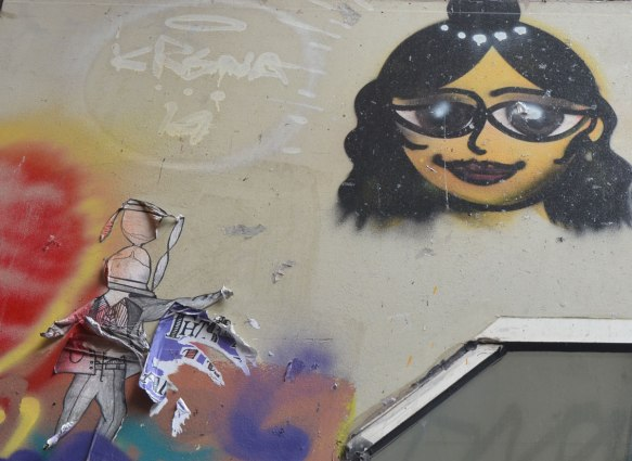 street art painting of a woman's head, shoulder length black hair, sunglasses and also a peeling paper wheatpaste