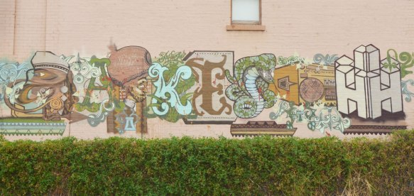 an interesting piece of street art, horizontal across a building, letters, but some animals incorporated into it. K E and S and H for sure but not sure what the other letters are.