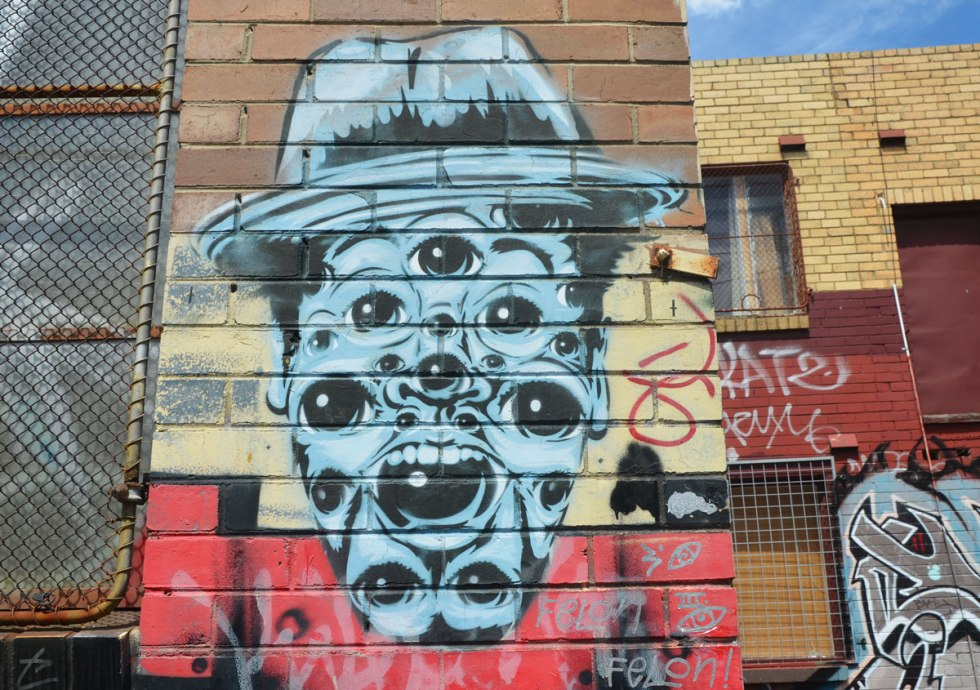 The likeness of a man wearing a hat. All in blue with black details, A mouth, a nose, and many many eyes, on a brick wall, street art