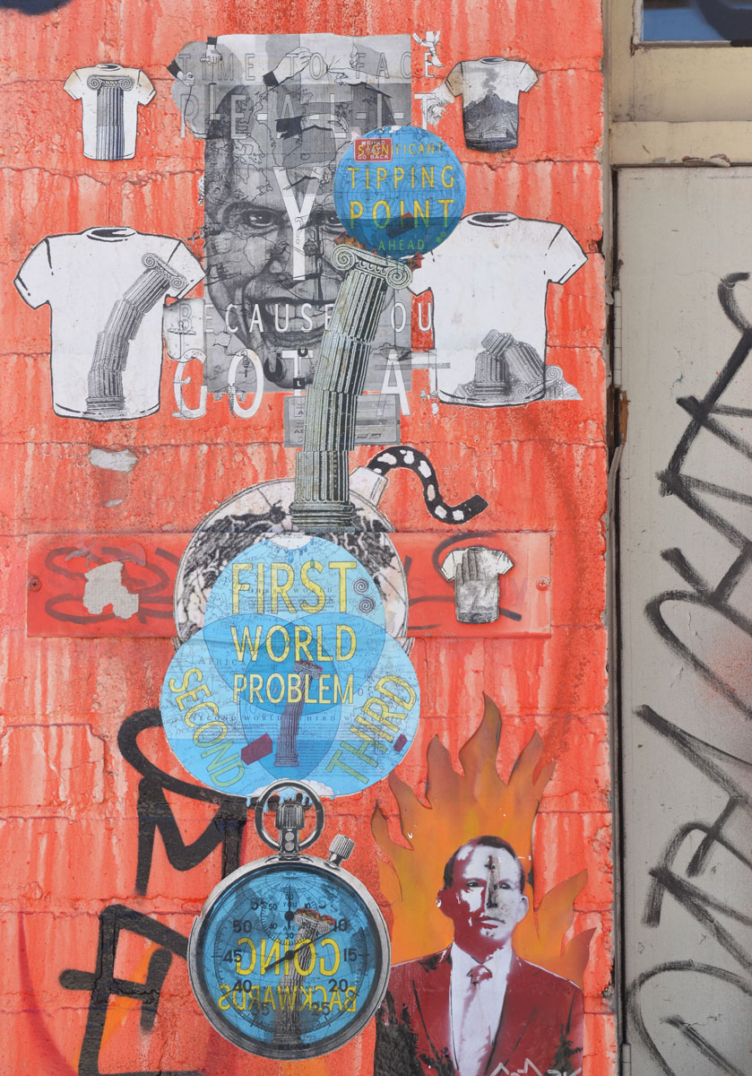 Many paste-ups on a part of a wall that has been painted orange.