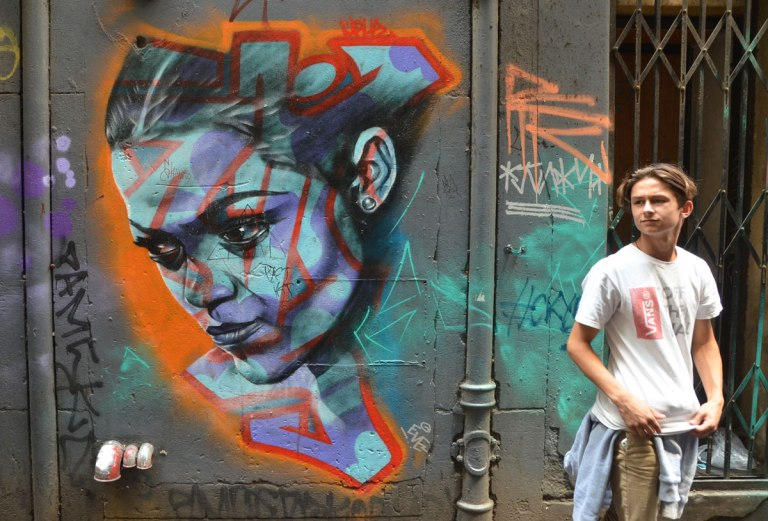 a realistic looking street art painting of a young woman's face in blues. A young man is standing beside painting, in a Melbourne alley