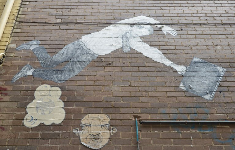 three wheatpaste graffiti pieces on a brick wall . On top is the largest, a man wearing a tie and holding a briefcase is diving horizontally, below him are two faces (both wheatpastes)