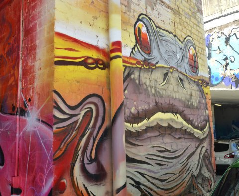 a street art painting of a frog partially submerged in water, his eyes are peaking out over the top of the water
