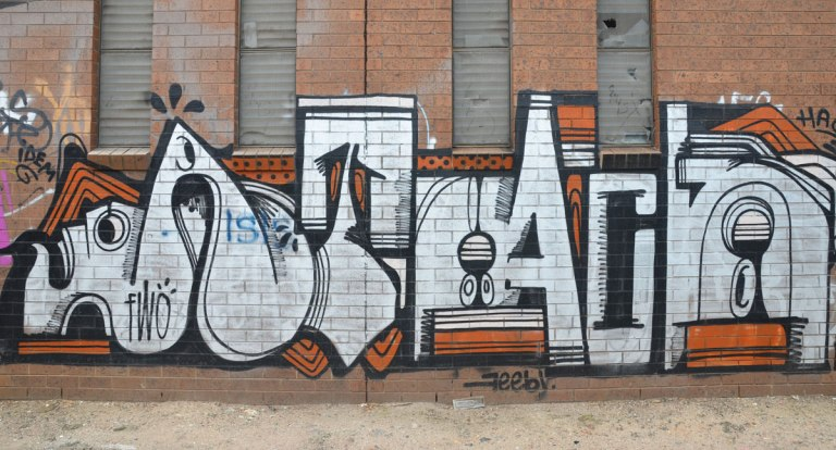 geometric tag in white letters with black and orange accents on a red brick wall. Small letters of the words fwo, feeby and idem