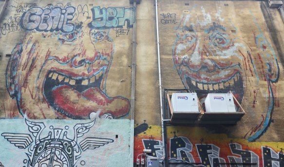 Two large faces painted high on a wall, the one on the left has a large tongue that is sticking out. Tagged Genie Yern, and yern genie.