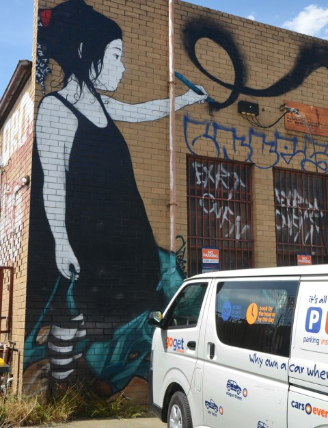 large mural of a girl with short black hair and black dress writing on the wall.