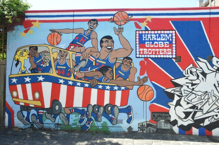 mural of Harlem globetrotters basketball team crowded into a red, white and blue bus.