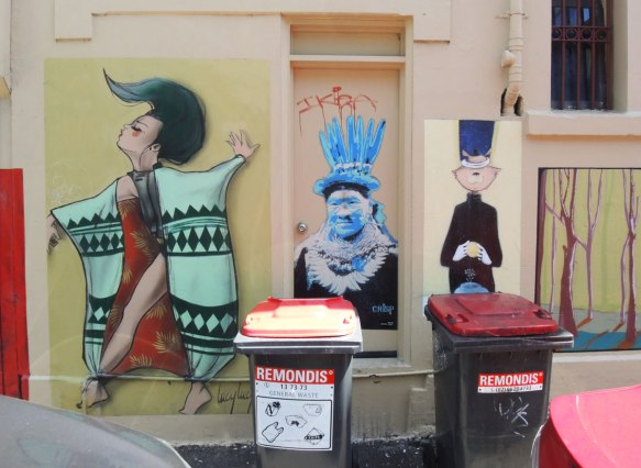 Three street art paintings - two on a wall and one in the middle on a door. On the left is a woman by artist Lucy Lucy, in the middle a person in black, white and blue, and on the right a rabbit like faced creatures, wearing a top hat