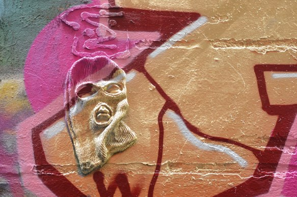 a balaclava mounted on a wall in an alley in such a way that it looks like a face, covered in pink and gold spray paint as part of a street art piece