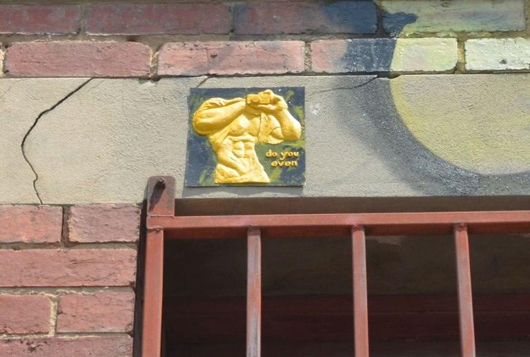 A small relief sculpture of a man's torso painted yellow, headless, large muscles, with hands clasped together in front of his chest holding onto a camera. The words Do you even are written under one elbow.