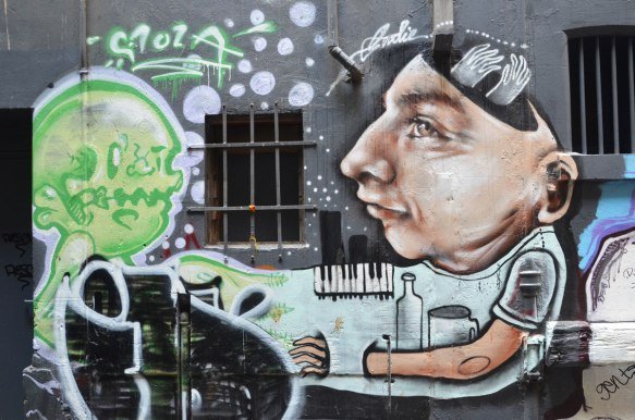 a young man painted by Goodie, with a piano keyboard and some empty bottles, a green creature by stola (Stoza?) is also in the picture