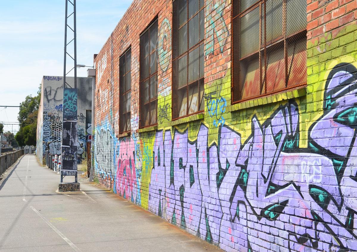 graffiti on a brick wall beside a bioke path and train tracks