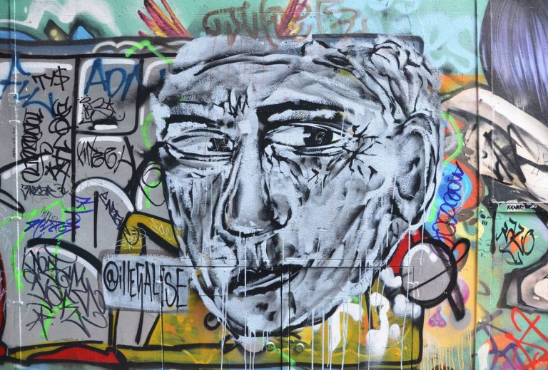 A grey man's face street art painting in Union Lane in Melbourne