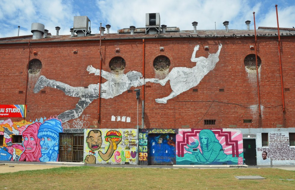 wall of an old red brick industrial building, 3 storeys high, covered with street art. Lower level is series of murals and above them is a large paste up by baby guerilla of a couple flying. A man is behind a woman and he is reaching for her foot as she is reaching for the roof of the building.