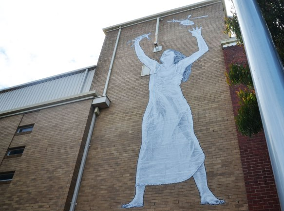 a large paste up of a woman in a long dress holding her hands in the air. In one hand is a helicopter and in the other hand is a small soldier. She is pasted high on a wall and she is about 10 or 12 feet high.