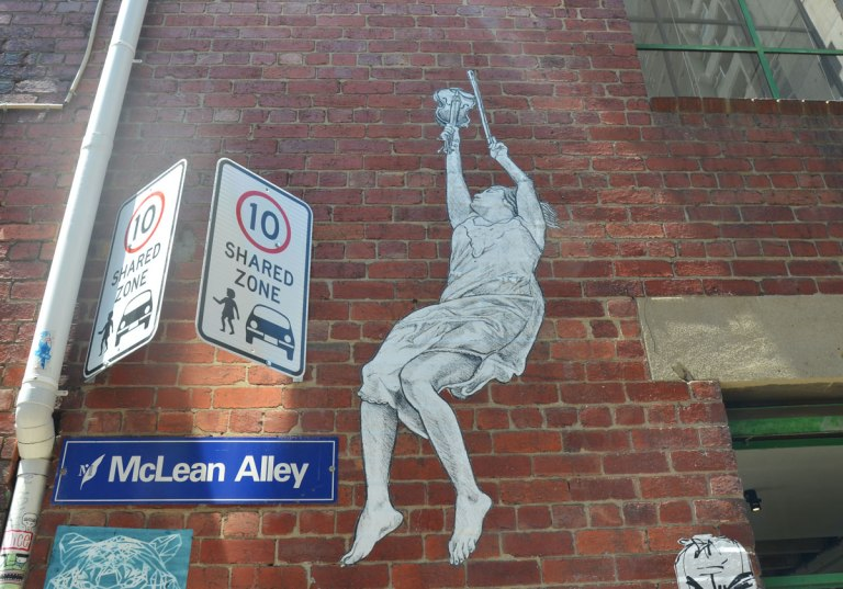 A paste up on a red brick wall of a girl reaching upwards with a violin in one hand and the bow for it in the other. By her feet is a blue and white sign saying McLean Way. No stopping signs are also in the picture.