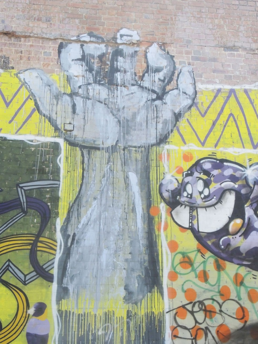 very large street art painting of an upstretched arm and open hand, in grey