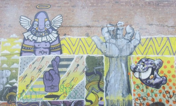 part of a larger mural, a hand and arm, as well as a purple hand with fingers crosses, also a purple man like creature.