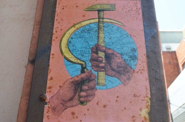 Paste-up of two pink hands, one holding a large hammer and one holding a large sickle. A blue globe (map of the world) is behind the hammer and sickle