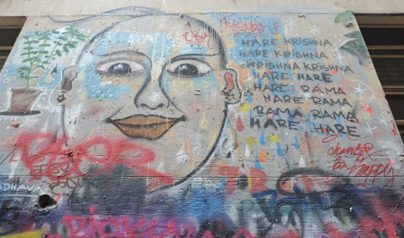 "In Union Lane, Melbourne, on a wall, a drawing of buddha's face with the words to Hare Krishna written beside it, along with ""be happy"""