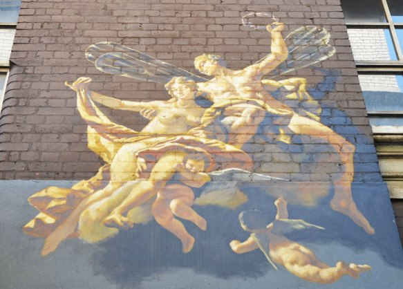 mural high on a brick wall, looks like an old fashioned painting of a heavenly scene, with angels and cherubs and men with wings. In gold tones.
