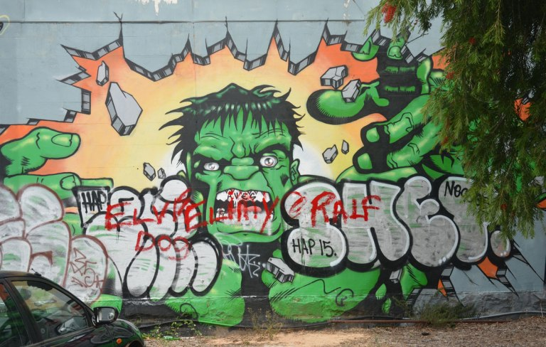 a street art painting of the Hulk (green man) smashing through a wall with just his hands.