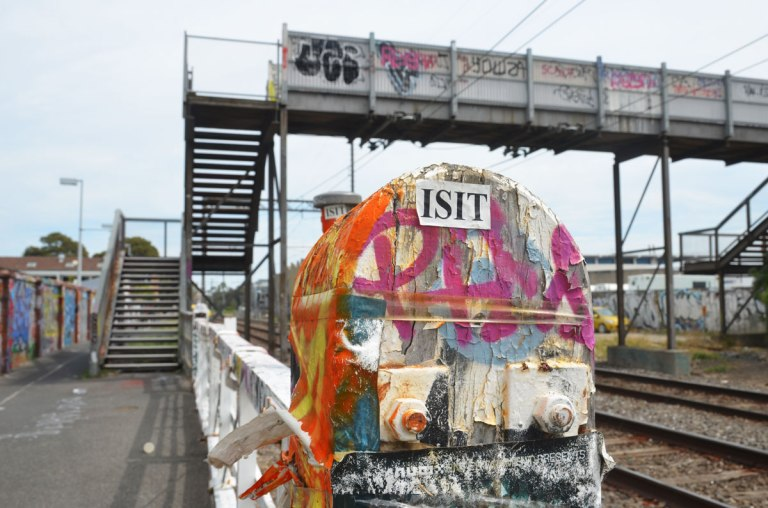 stickers covering a fence post, also spray paint in orange and pink. A white rectangular sticker with ISIT printed on it. In the background, slightly out of focus, is a pedestrian bridge over railway tracks