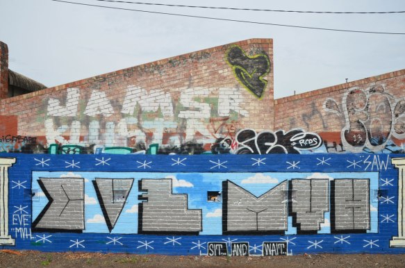 "row of old brick buildings with diagonal rooflines covered with graffiti beside a bike path near Jewell train station - large text graffiti that says Eve MVH and the words ""sit and wait"" written underneath. Jamsr Klustr written in large letters above it."