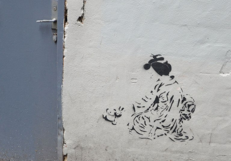 stencil graffiti of an Asian woman (Japanese?) crouching on the ground wearing a kimono, with her hair tied up. On a white wall beside a blue door